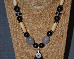 Un collier Mixte, en Bois Ebène, monté avec des graines de Savonnette, Canic grise, Courbaril.
