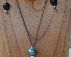 Ce sautoir réglable monté sur un lacet de daim marron, perle céramique et graine Wa-Wa et ti coco.